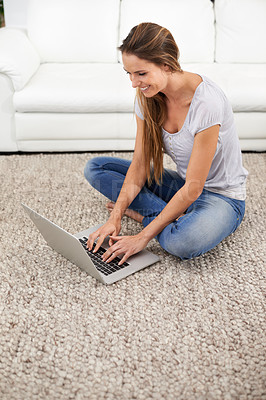 Buy stock photo Shot of a woman sitting on her living room carpet while using her laptop
