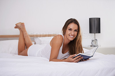 Buy stock photo Portrait of a beautiful young woman reading a book while lying on her bed