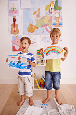 Buy stock photo Portrait of two cute little boys holding up their artwork at home
