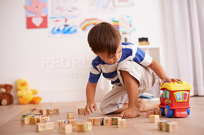 Buy stock photo Shot of a little boy playing with his building blocks and toy truck in his room