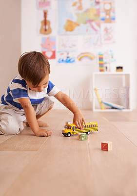 Buy stock photo Shot of a cute little boy playing with his toys in his room
