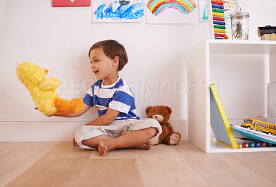 Buy stock photo Shot of a little boy playing with his toys in his room