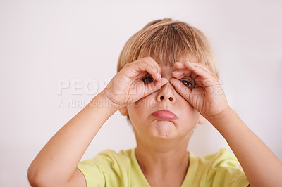 Buy stock photo Shot of a cute little boy standing with his hands cupped around his eyes