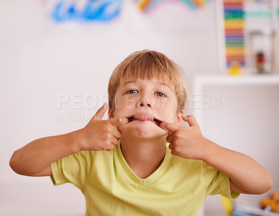 Buy stock photo A little boy pulling a face