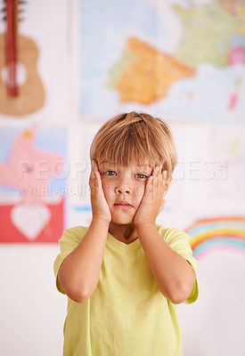 Buy stock photo A young boy holding his face in his hands with a worried expression