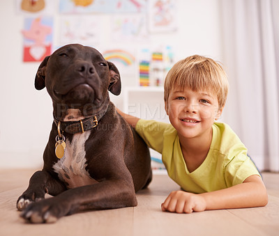 Buy stock photo A little boy playing with his dog in his room