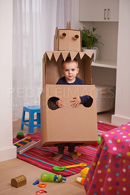Buy stock photo A young boy playing with a cardboard box cut into the shape of a robot