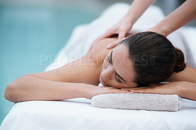Buy stock photo Shot of a woman enjoying a massage beside a pool