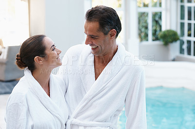 Buy stock photo Shot of a couple in robes beside a pool