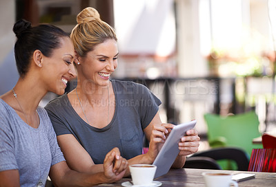 Buy stock photo Two young women looking at a tablet in a coffee shop