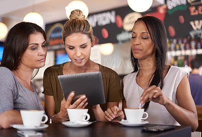 Buy stock photo Three attractive young women gathered around a tablet pc in a restaurant