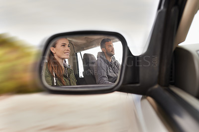 Buy stock photo Cropped hot of a young couple on a road trip reflected in a car's side mirror