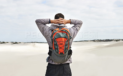 Buy stock photo Rearview of a young male hiker walking along the sand dunes