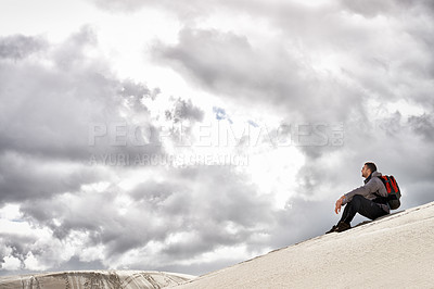 Buy stock photo Shot of a handsome male hiker sitting on the sand dunes