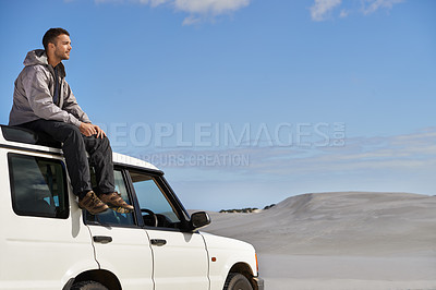 Buy stock photo Cropped shot of a young man sitting on the roof of his car while on a roadtrip