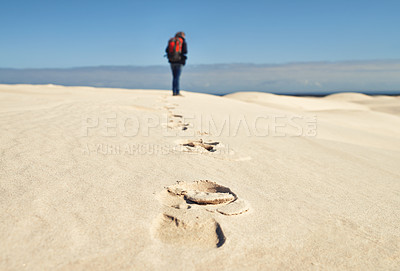 Buy stock photo Rearview of a young female hiker walking along the sand dunes