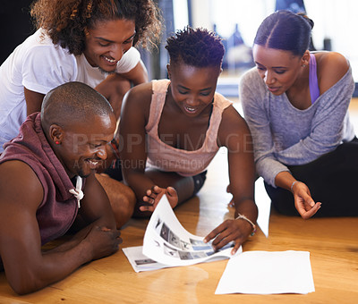 Buy stock photo Shot of a group of young dancers looking through a catalogue of dance moves