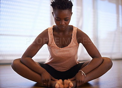 Buy stock photo Shot of a young woman dancer stretching in a studio