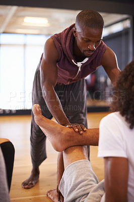 Buy stock photo Shot of a dance instructor helping his student to warm up in a dance