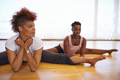 Buy stock photo Shot of two young women dancer stretching on the floor