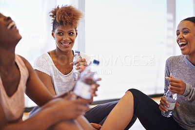 Buy stock photo Shot of a group of happy young dancers sitting on the floor of their dance studio