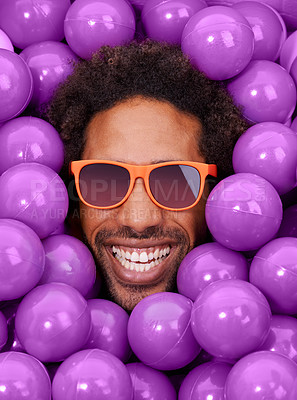 Buy stock photo A young black man's face amongst purple pit balls