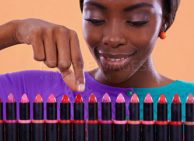 Buy stock photo A young african woman looking over a row of colorful lipsticks