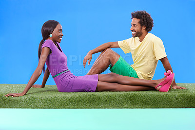 Buy stock photo A young african couple sitting on the grass together