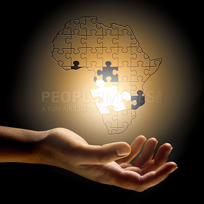 Buy stock photo Conceptual shot of a person's hand building a puzzle in the shape of Africa