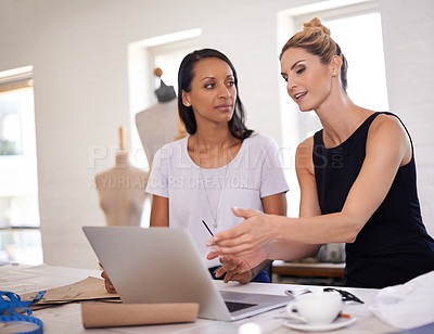 Buy stock photo Two young fashion designers discussing a design