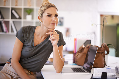 Buy stock photo A confident young businesswoman sitting at her desk looking thoughtful