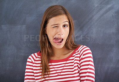 Buy stock photo Cropped shot of a young woman sticking her tongue out