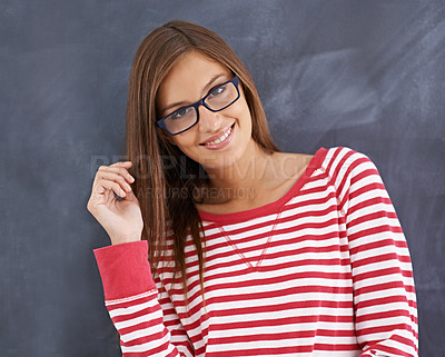 Buy stock photo Portrait of a gorgeous young woman standing in front of a blackboard