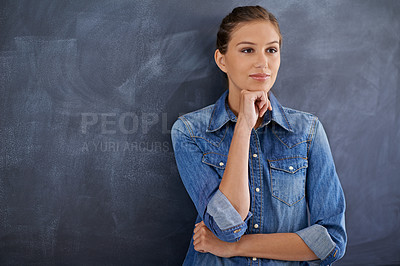 Buy stock photo Shot of a thoughtful young woman standing in front of a chalk board