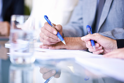Buy stock photo Cropped view of a group of businesspeople working at a table on some documents