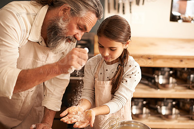 Buy stock photo Shot of a girl bonding with her grandfather as they bake in the kitchen