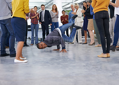 Buy stock photo Shot of a man breakdancing in an office full of employees