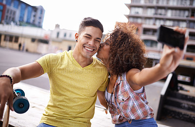 Buy stock photo A young couple taking a selfie while out skateboarding