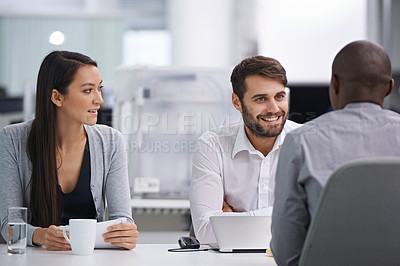 Buy stock photo Three happy coworkers sitting down to have a meeting