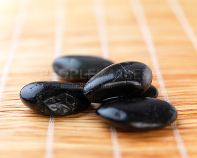 Buy stock photo Close up shot of several hot stones on a mat, from the beauty spa