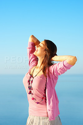 Buy stock photo Pretty young woman relaxing with hands behind head against sky