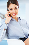 Smiling female executive talking on cellphone