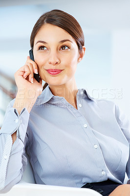 Buy stock photo Happy young businesswoman sitting on chair and using mobile phone