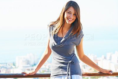 Buy stock photo Portrait of cute young girl standing on the balcony and smiling