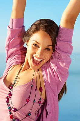 Buy stock photo Portrait of beautiful young girl standing against sky with hands raised
