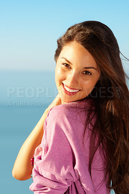 Buy stock photo Portrait of beautiful young woman standing against sky and giving you an attractive smile