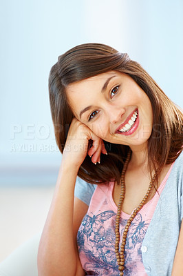 Buy stock photo Portrait of young woman relaxing on chair and giving you an attractive smile