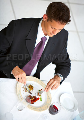 Buy stock photo Shot of a man in a suit eating a meal in a restuarant