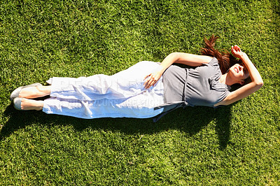 Buy stock photo Top view of young girl relaxing in grass with hand on head