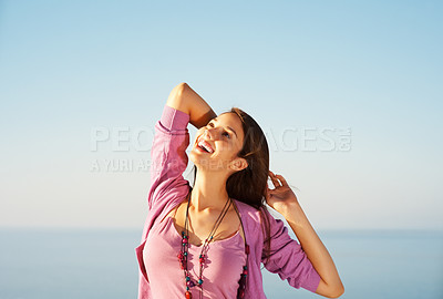 Buy stock photo Young female looking upwards and enjoying the sun with hands behind head